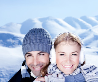 Happy couple hugs, holding hands, close up face portrait, outdoor at winter snowy mountains, people over natural blue wintertime landscape background, Christmas vacation holidays, love concept