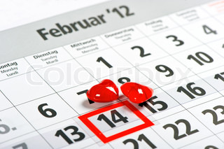 calendar with red mark on 14 February and red hearts decoration