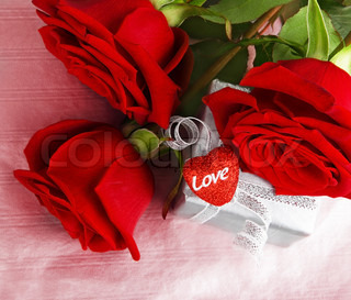 Romantic gift & red roses, isolated on pink background, love concept