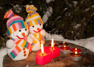 Two snowmen with two burning heart shaped candles staying outdoors