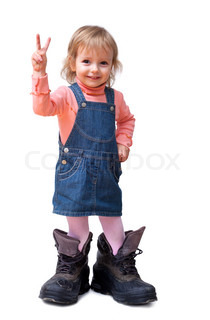 Smiling cute little girl in old big tracking shoes shows V-sign isolated on white