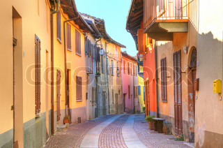 Narrow paved street among old multicolored houses in town of Serralunga D'Alba in Piedmont, Northern Italy