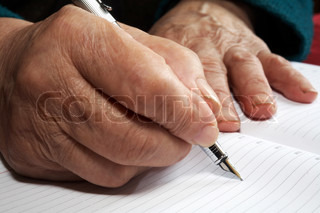 Old hands writing with an ink pen in a notebook