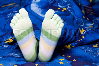 Stock photo: an image of funny feet in green striped socks