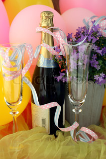 champagne bottle, glasses and serpentines in front of balloons