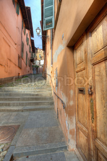 Vertical oriented image of wooden door and narrow paved street among old houses in town of Saluzzo, northern Italy