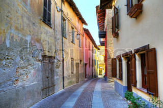 Narrow paved street among old abandoned house from one side and renovated from other in small town of Serralunga D'Alba in Northern Italy