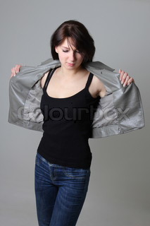 woman in jeans and leather jacket over grey background