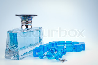 Blue beads and bottle perfume on white