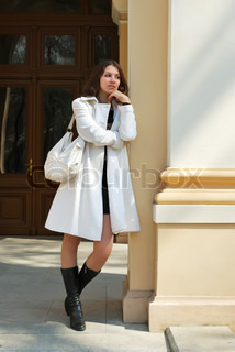 beautiful girl standing pensively at the column