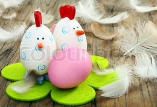 Funny Easter eggs and feathers on a wooden board