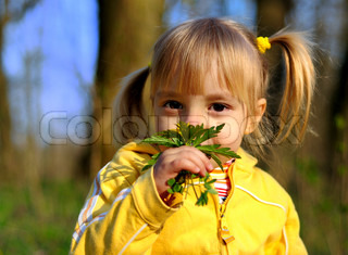 The little girl with a bouquet of spring flowers in wood