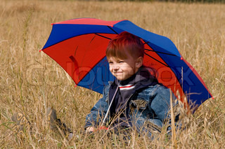 Little boy with his umbrella in autumn day