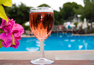 The glass of pink wine near swimming pool