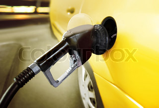 yellow car at gas station being filled with fuel