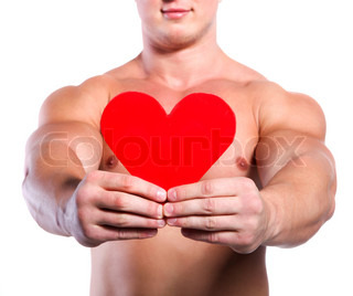 Strong muscular man holding red valentine's heart at white background
