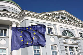 European Union flag in front of a gray office building in classical style