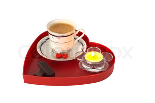 Romantic breakfast with chocolate on red heart shaped tray with small candle
