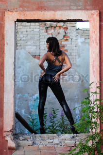 Woman in tight black leather outfit striking sexy stance in old cement doorway