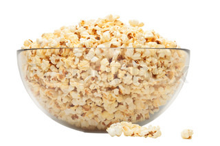 popcorn in glass bowl over white background