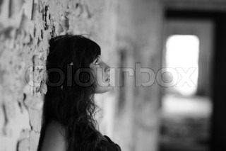 Monochrome image of a lonely young girl in profile leaning against an old stone wall, head and shoulders outdoor portrait