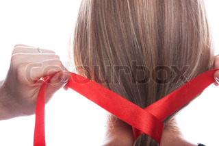 Young woman braids her hair with red ribbon