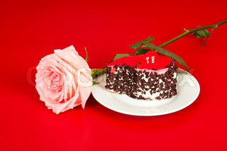 Pink rose and sweet cake on dish, red background