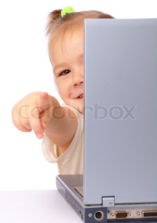 Cute little girl is looking out from her laptop and pointing at you, isolated over white