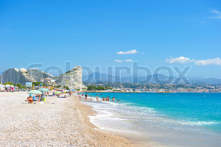View of the beach in Nice, France, Cote d'Azur tourists, sunbeds and umbrellas on summer hot day on the beach
