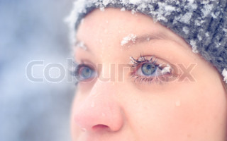 Girl's face under snow outdoors. Close up portrait