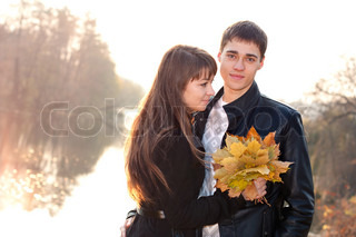 Young beautiful happy smiling couple in love against the background of backlit beauti autumn nature