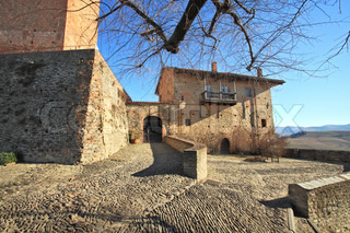 Paved stoned courtyard, old brick house at the entrance to castle in town of Serralunga D'Alba, Northern Italy