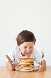 Greedy boy with pancakes