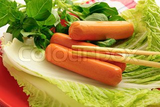 Boiled sausage with green cabbage and basil leaves - food background