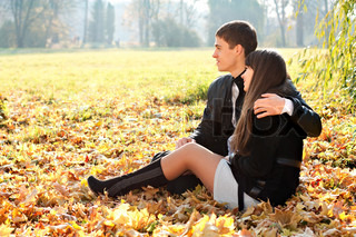 Young couple in love hugging against the background of beautiful sunny autumn nature