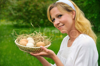 Smiling young woman holding fresh eggs – outdoor