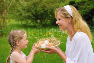 Woman and little girl holding fresh eggs - outdoor
