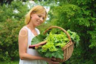 Happy young woman holding basket with vegetable – lettuce, rhubarb, spinach – outdoor