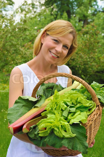 Smiling young woman holding basket with vegetable – lettuce, rhubarb, spinach – outdoor