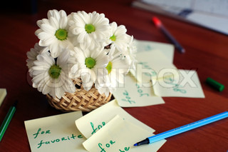 An image of basket with white daisies on the desk
