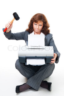 Business woman in formal clothes angry on her printer and crushing it with hammer