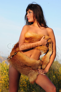 Attractive naked woman posing on the skyline with fur wound around her breasts and loins, implied nude