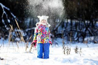 Toddler girl in colorful snowsuit plays in snow on sunny winter day