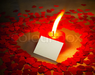 Burning heart shaped candle and a card with 'I love you' writing