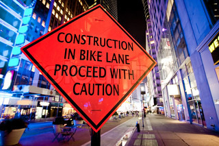 Construction in bike lane proceed with caution sign in New York City