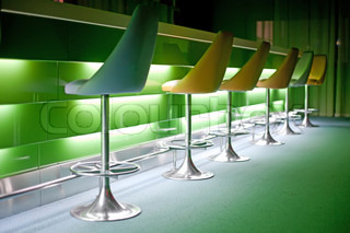 Chairs in row in bar with green lights