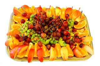 dessert of fruit and berries on a tray on a white background
