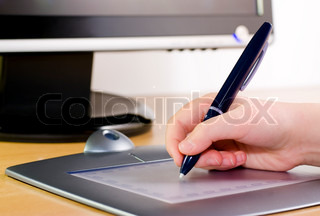 Hand holding pen on wireless tablet