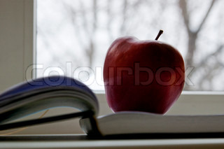 An apple lay on book next to window