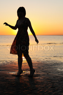 Portrait of young woman as silhouette by the sea
